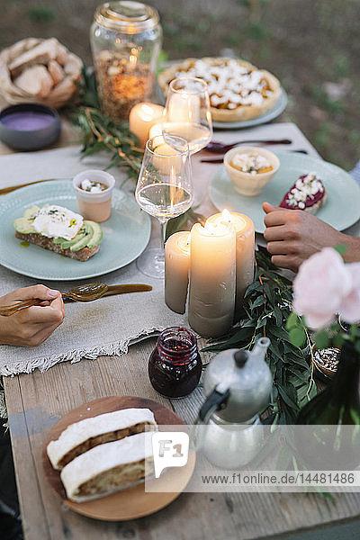 Nahaufnahme eines Paares bei einem romantischen Essen bei Kerzenlicht im Freien