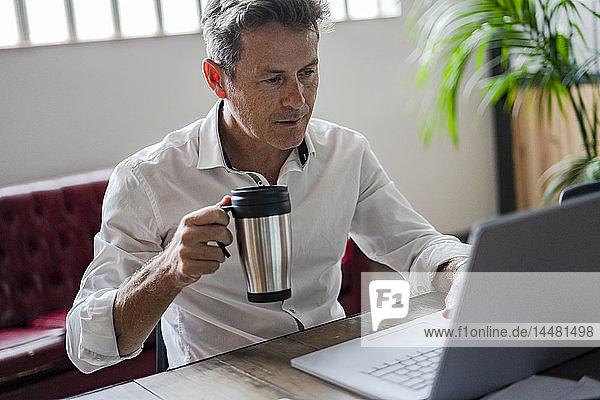 Businessman holding coffee mug using laptop at desk