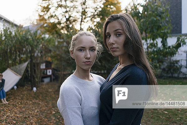 Porträt von zwei ernsthaften Teenager-Mädchen im Garten