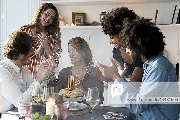 Freunde feiern den Geburtstag einer jungen Frau,  blasen Geburtstagskerzen aus