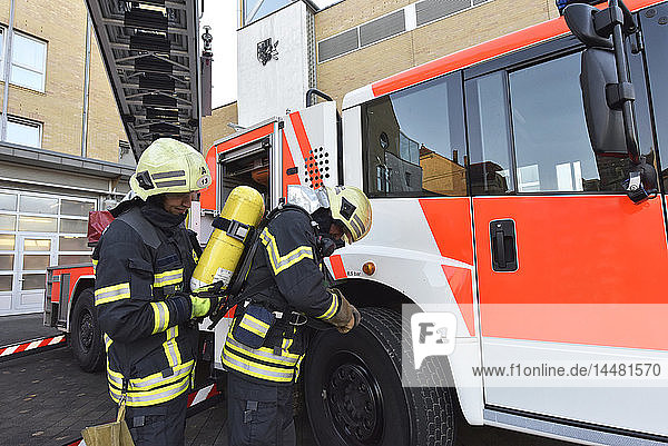 Two firefighters at fire engine preparing for an operation