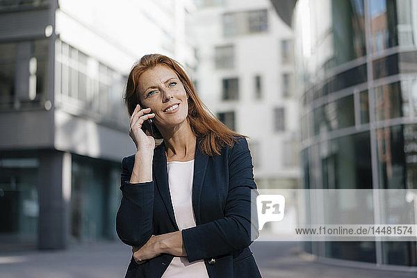 Lächelnde Geschäftsfrau am Handy im Freien in der Stadt