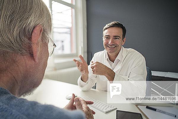 Lächelnder Arzt im Gespräch mit Patient in der medizinischen Praxis