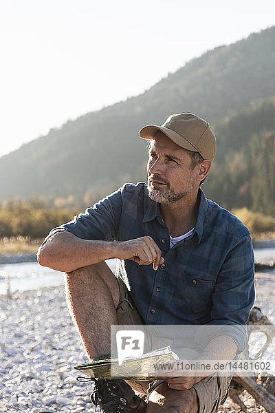 Erwachsener Mann zeltet am Flussufer  sitzt auf Baumstamm mit Karte