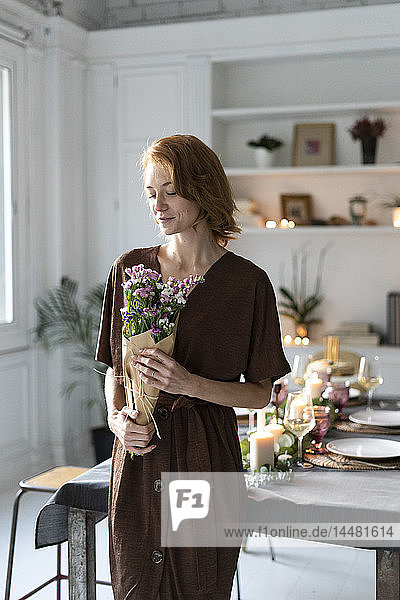 Redheaded woman holding bunch of flowers  standing in front of laid table