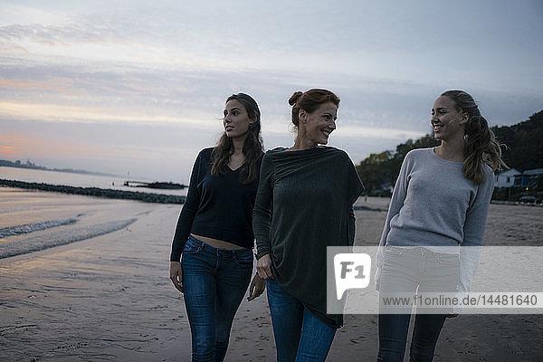 Deutschland  Hamburg  glückliche Mutter mit zwei Teenager-Mädchen  die abends am Strand am Elbufer spazieren gehen
