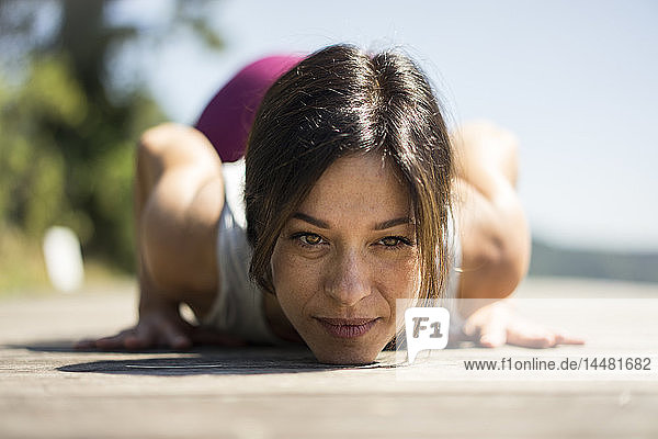 Mature woman practicing yoga in summer on a jetty