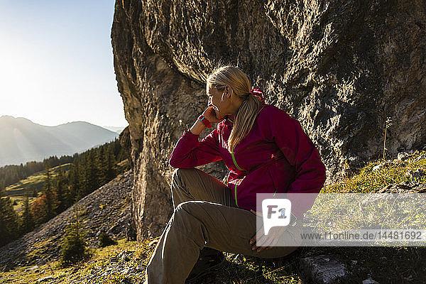 Frau sitzt in den Bergen und genießt die Aussicht