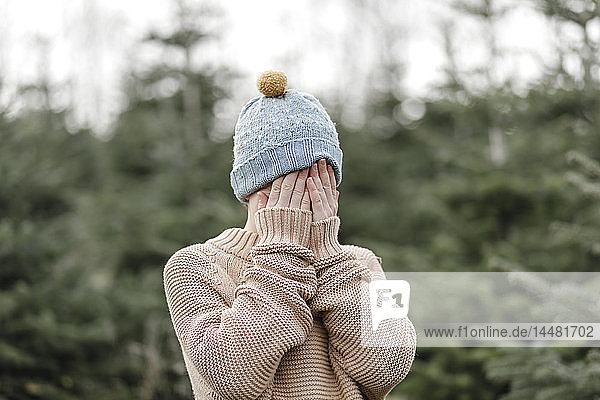 Junge mit Wollmütze  die sein Gesicht bedeckt