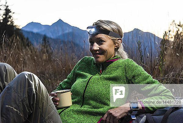 Wandernde Frau macht eine Pause  trinkt Tee  trägt Stirnlampe