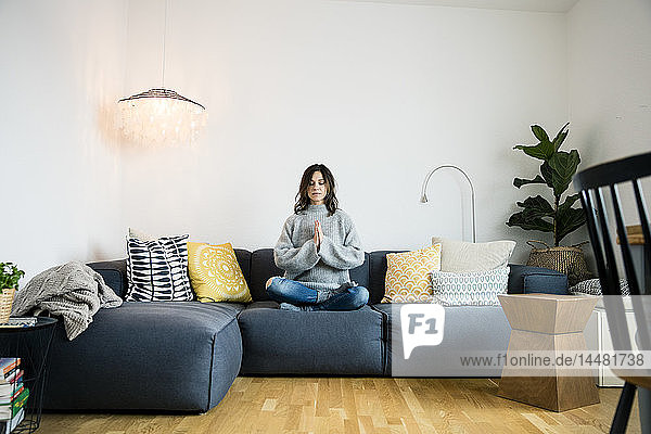 Mature woman sitting cross-legged on couch with eyes closed  meditating at home