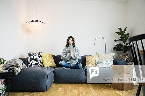 Reife Frau sitzt im Schneidersitz mit geschlossenen Augen auf der Couch und meditiert zu Hause