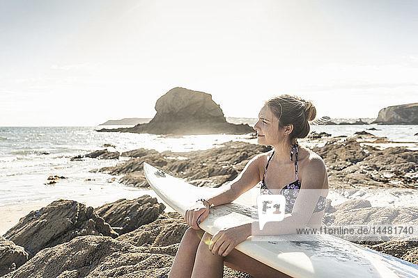 Junge Frau mit Surfbrett entspannt am Strand  auf einem Felsen sitzend