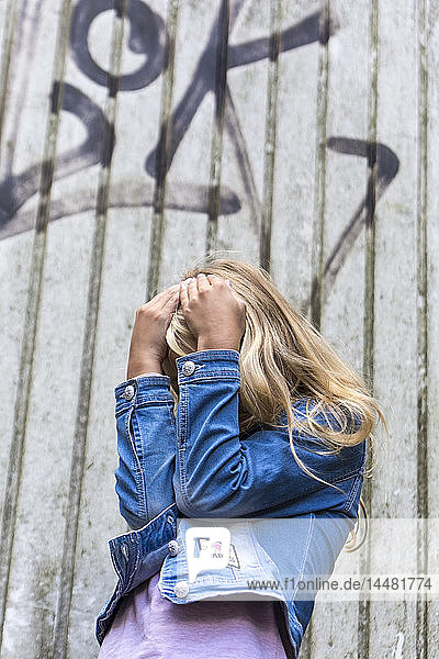 Blond girl hiding her face