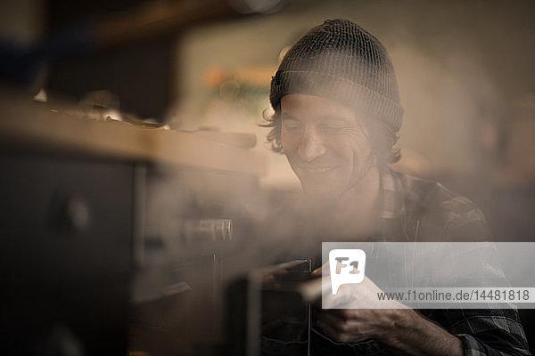 Mann öffnet dampfenden Ofen in seiner Küche