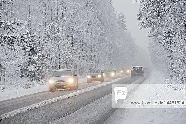 Autos fahren im Winter auf der Landstraße  es schneit