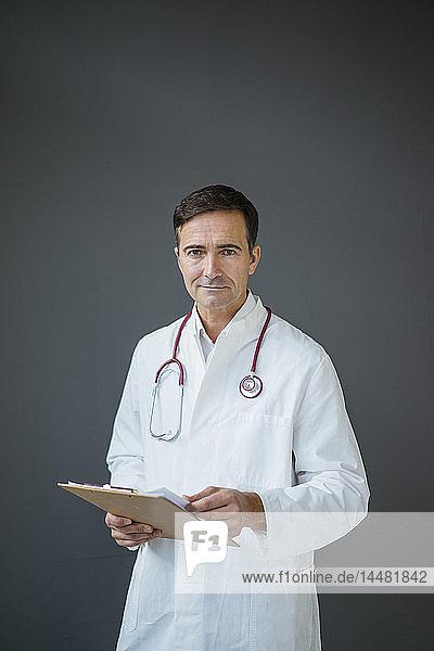 Porträt eines selbstbewussten Arztes  der ein Klemmbrett an einer grauen Wand hält