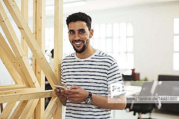 Porträt eines lächelnden jungen Mannes mit Handy im Büro