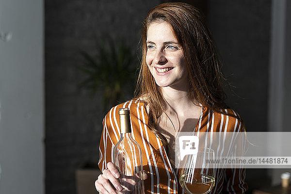 Junge Frau mit Weinflasche in der Hand  Porträt
