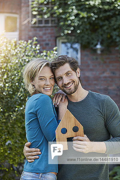 Portrait of happy couple in front of their home with house model