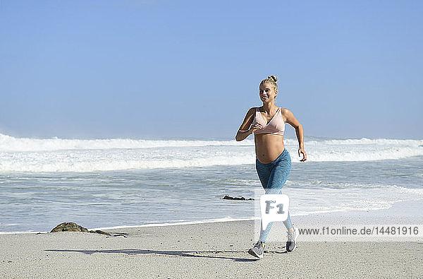 Lächelnde schwangere Frau joggt am Strand