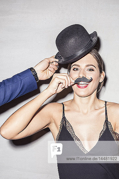 Portrait of young woman with bowler and fake moustache at a party