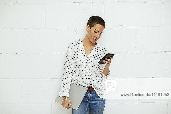 Junge Frau steht an Ziegelmauer und schaut auf Handy