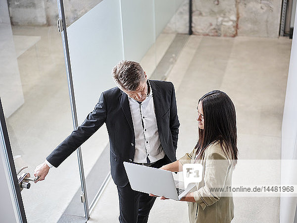 Businessman and businesswoman meeting with laptop at the door in office