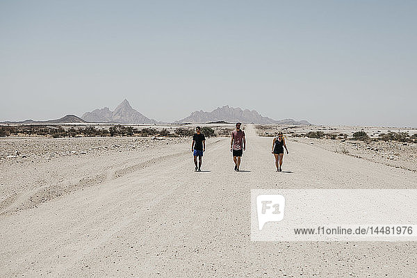 Namibia  friends walking on the road to Spitzkoppe