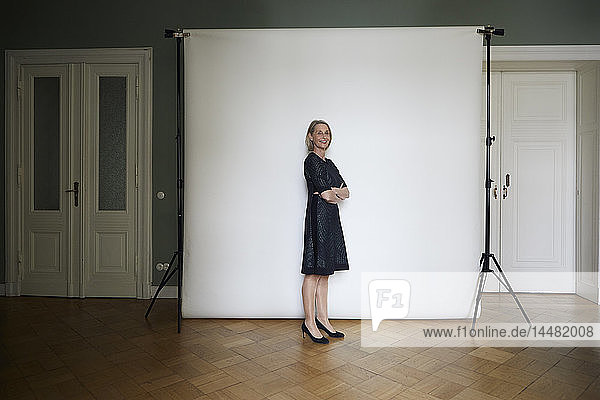 Portait of confident mature woman posing at projection screen