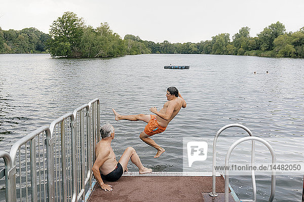 Mann springt vom Steg in einen See