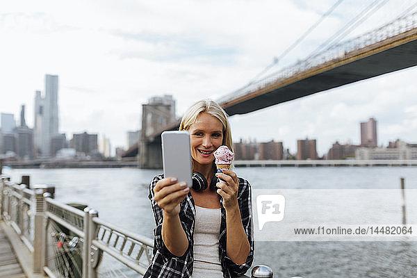 USA  New York City  Brooklyn  lächelnde junge Frau  die am Wasser steht  ein Eis isst und ein Selfie nimmt