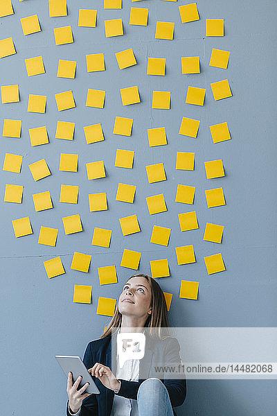 Junge Geschäftsfrau nutzt digitales Tabet  sitzt unter der Datenwolke