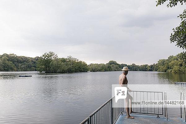 Älterer Mann mit Strohhut steht an einem See