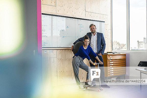 Älterer Mann und sein Assistent mit Roller  stehen im Büro vor dem weißen Brett