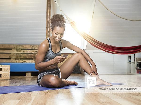 Lächelnde junge Frau sitzt auf Yogamatte und schaut auf Handy