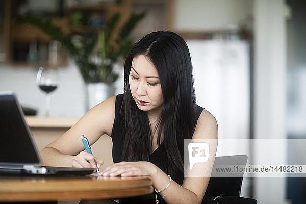 Junge Frau in schwarzem Kleid benutzt Laptop und macht Notizen auf dem Tisch zu Hause