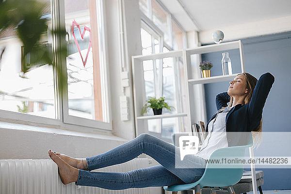 Junge Geschäftsfrau  die sich im Büro bewegt  am Fenster sitzt und die Füße hochgelegt hat