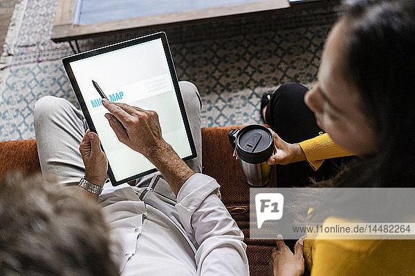 Geschäftsfrau und Geschäftsmann teilen sich ein Tablett auf dem Sofa im Loft-Büro
