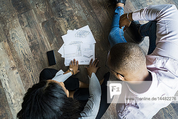 Top view of businessman and businesswoman sitting on the floor discussing documents