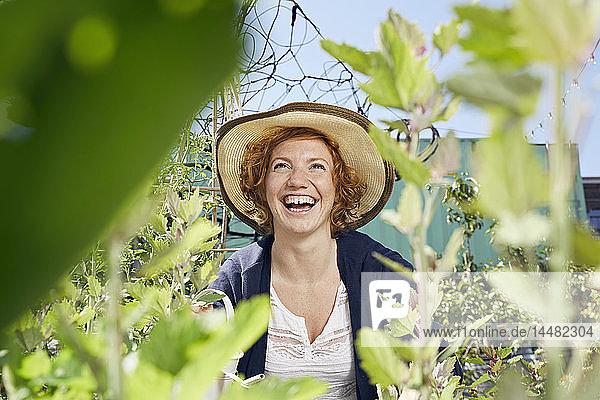 Porträt einer glücklichen jungen Frau mit Stroh im Stadtgarten