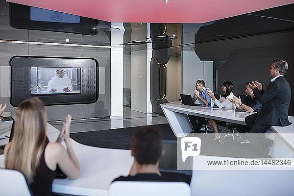 Geschäftsleute applaudieren internationalen Kunden in Videokonferenz