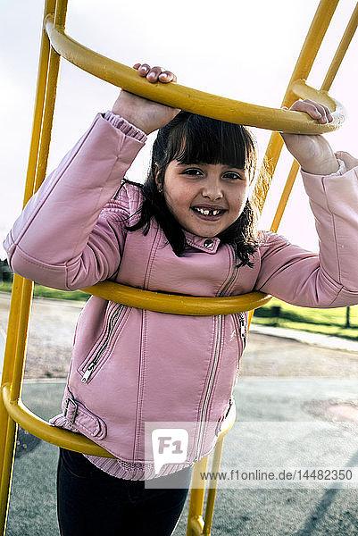 Porträt eines Mädchens mit Zahnlücke in rosa Lederjacke auf dem Spielplatz