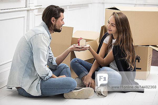 Mann übergibt winziges Hausmodell an Freundin  umgeben von Pappkartons