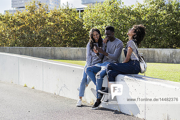 Drei Freunde verbringen Zeit in der Stadt und benutzen ein Smartphone