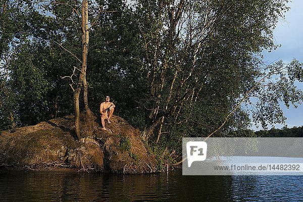 Mann sitzt auf einer Insel in einem See