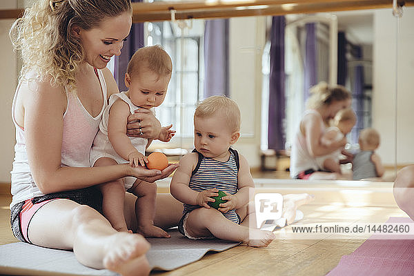 Mother with playing twin babies sitting on yoga mat