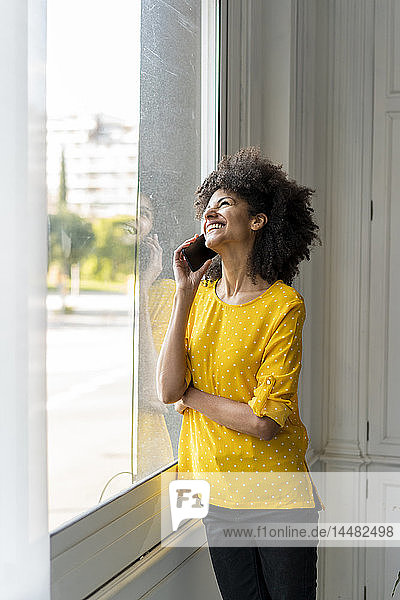 Frau steht am Fenster und telefoniert