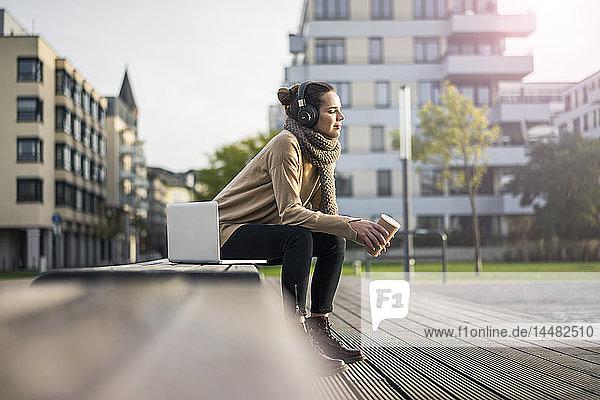 Frau mit Kaffee  um im Herbst auf einer Bank zu sitzen und mit Laptop und schnurlosen Kopfhörern Musik zu hören