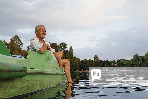 Älterer Mann sitzt auf einem Tretboot auf einem See